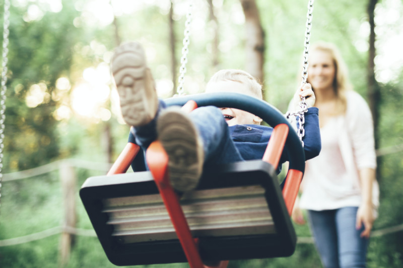 Mother and child outdoors in playground riding a swing and smiling